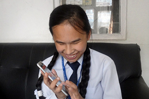 Photo, a blind student in Nepal listening to school textbooks adapted into audio form.